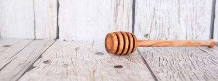 dipper: Wooden honey dipper over wooden background