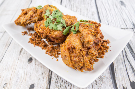 javanese: Popular Javanese dish Ayam Penyet or crispy fried chicken in a white plate over wooden background