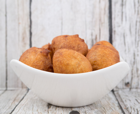 balls deep: Popular Malaysian fritter snack deep fried banana balls or locally known as Cekodok Pisang in white bowl over wooden background