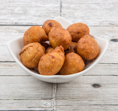 fritter: Popular Malaysian fritter snack deep fried banana balls or locally known as Cekodok Pisang in white bowl over wooden background
