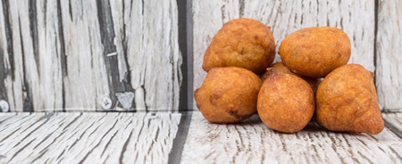balls deep: Popular Malaysian fritter snack deep fried banana balls or locally known as Cekodok Pisang over wooden background