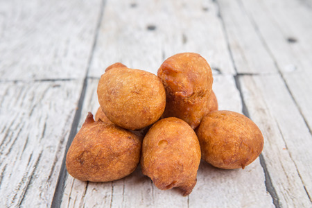 fritter: Popular Malaysian fritter snack deep fried banana balls or locally known as Cekodok Pisang over wooden background