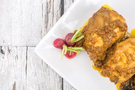 Malaysian dish Rendang Ayam or dry curry chicken in a white plate over wooden background Reklamní fotografie