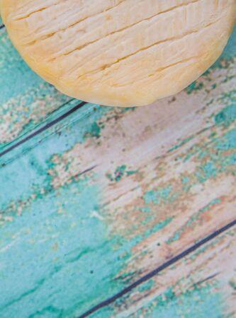 grasas saturadas: Queso redondo sobre fondo de madera