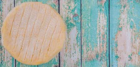milk products: Round cheese over wooden background