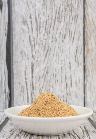 repellant: Lemongrass powder in a white bowl over wooden background