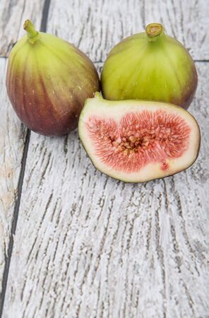 sweet segments: Fig fruits over wooden background