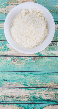 grated parmesan cheese: Grated cheese in white bowl over wooden background Stock Photo