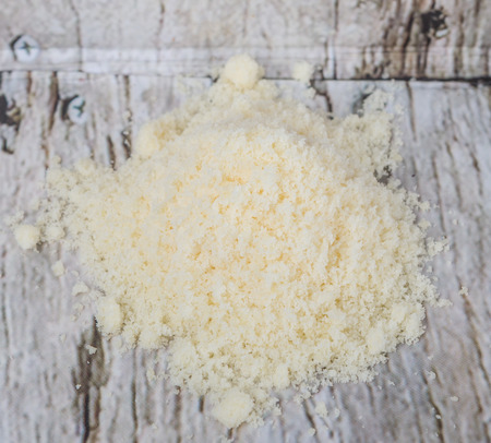 queso rallado: Queso rallado sobre fondo de madera