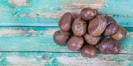 flesh colour: Roasted whole peeled chestnut over wooden background