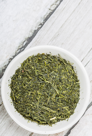 sencha: Dried green tea leaves in white bowl over wooden background