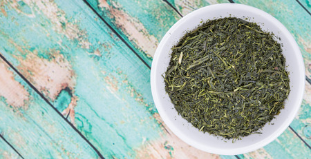 sencha tea: Dried green tea leaves in white bowl over wooden background