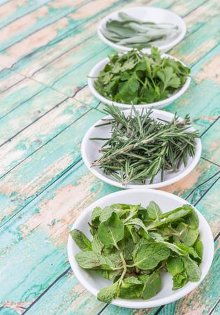 Rosemary, menthe, persil et feuilles de sauge herbes dans un bol blanc sur fond de bois