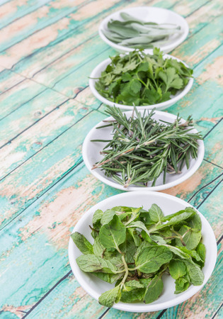 green herbs: Rosemary, mint, parsley and sage leaves herbs in white bowl over wooden background