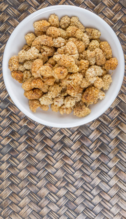 superfruit: Dried white mulberry in a white bowl over wicker background Stock Photo