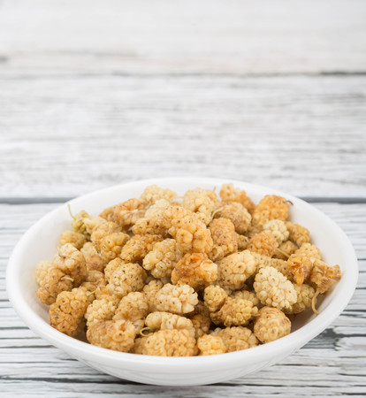 superfruit: Dried white mulberry in white bowl over wooden background