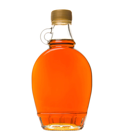 becf0b8420f Maple syrup in a glass bottle over white background