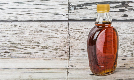 Maple syrup in a glass bottle over wooden background