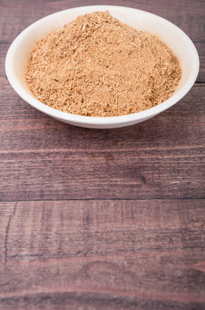 galangal: Dried galangal powder in white bowl over wooden background
