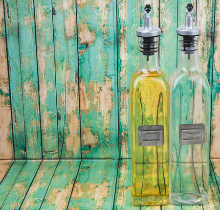 acetic: Vegetable cooking oil and white vinegar in glass bottles over wooden background