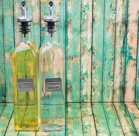 acetic: Vegetable cooking oil and white vinegar in a glass bottles over wooden background Stock Photo