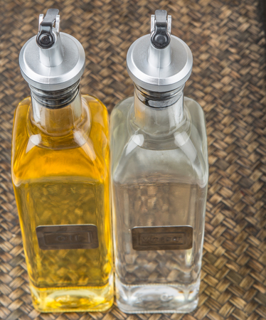 acetic: Vegetable cooking oil and white vinegar in a glass bottles over wicker background Stock Photo
