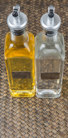 acetic acid: Vegetable cooking oil and white vinegar in a glass bottles over wicker background Stock Photo