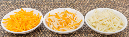 grated  mozzarella cheese: Grated mozzarella and cheddar cheese in white bowls over wicker background Stock Photo