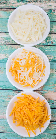 grated  mozzarella cheese: Grated cheddar and mozzarella cheese in white bowl over wooden background