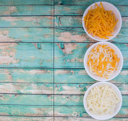 grated mozzarella cheese: Grated cheddar and mozzarella cheese over wooden background