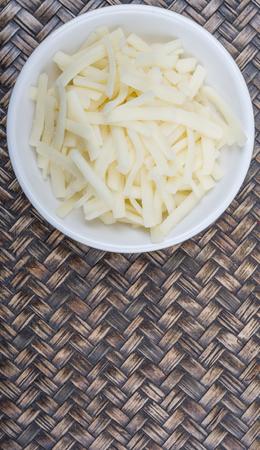 grated mozzarella cheese: Grated mozarella cheese in white bowl over wicker background