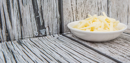 grated mozzarella cheese: Grated mozzarella cheese in white bowl over wooden background Stock Photo