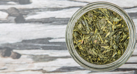 japanese green tea: Dried Japanese green tea leaves in a mason jar over wooden background Stock Photo