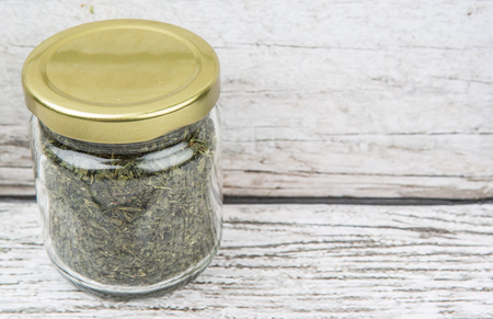 nutritional therapy: Dried Japanese green tea leaves in a mason jar over wooden background Stock Photo