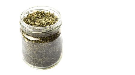 japanese green tea: Dried Japanese green tea leaves in mason jar over white background