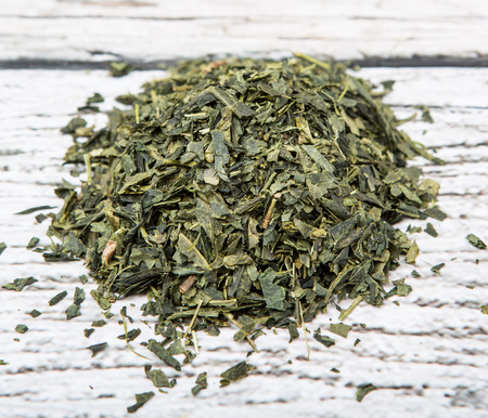 nutritional therapy: Dried Japanese green tea leaves over wooden background