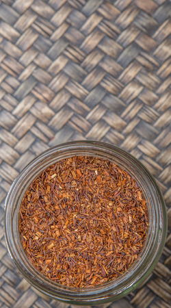 red bush tea: Dried rooibos herbal tea in mason jar over wicker background