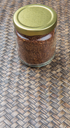 red bush tea: Dried rooibos herbal tea in mason jar over wicker background