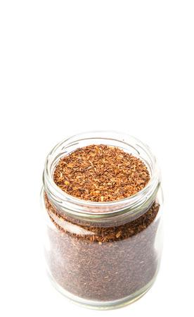 red bush tea: Dried rooibos herbal tea in mason jar over white background