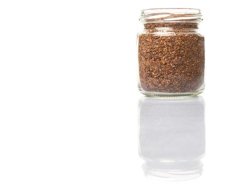rooibos: Dried rooibos herbal tea in mason jar over white background
