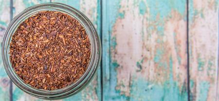 red bush tea: Dried rooibos herbal tea in mason jar over wooden background