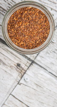 red bush tea: Dried rooibos herbal tea in mason jar over wooden background
