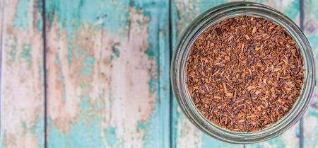 rooibos: Dried rooibos herbal tea in mason jar over wooden background