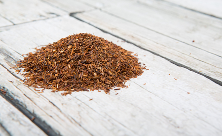 Dried rooibos herbal tea over wooden background