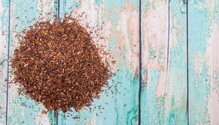 rooibos: Dried rooibos herbal tea over wooden background