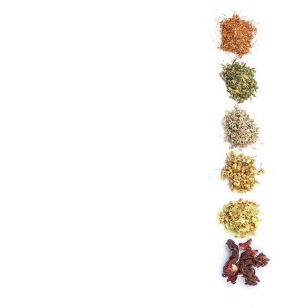 herbal background: Dried herbal tea leaves, lavender, rooibos, chamomile, linden flower, hibiscus, Japanese green tea over white background