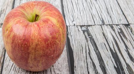 Fresh Japanese Fuji apple over wooden background