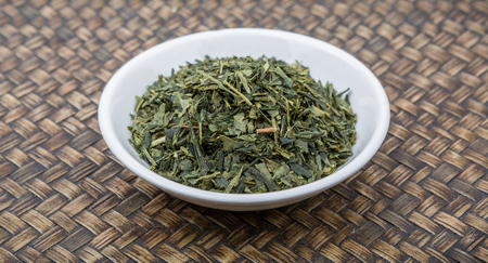 nutritional therapy: Dried Japanese green tea leaves in white bowl over wooden background