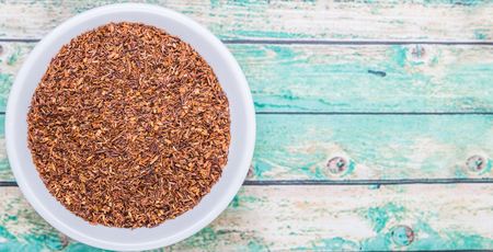 rooibos: Dried rooibos herbal tea leaves in white bowl over wooden background