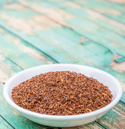 rooibos: Dried rooibos herbal tea in white bowl over wooden background